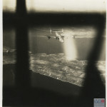 A view of a B-24 through the window of another B-24. Both are powered by Pratt & Whitney Twin Wasp engines.