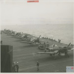 A line of Vought F4U Corsairs rest on a carrier in the Pacific Ocean. The Corsair was powered by the Pratt and Whitney Double Wasp. There is a Corsair on exhibit in the U.S. Freedom Pavilion: Boeing Center at the NWWII Museum.