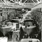 "View of a Higgins boat assembly line, sign above factory reads ""The guy who relaxes helps the axis."" Louisiana in the 1940s. From the collection of The National WWII Museum."