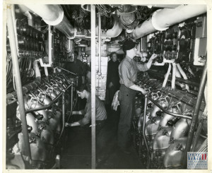 Life aboard a US Navy submarine. American submarines are powered by diesel engines when operating on the surface. Here machinist mates check the mammoth twin Diesels in the engine room of a U.S. sub.