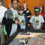 Students watch their robot track its way across the mat.