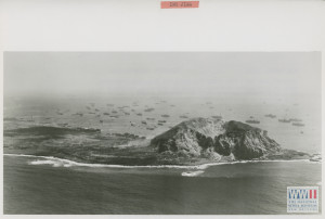 Aerial view of Mount Suribachi on Iwo Jima showing US landings taking place on February 24, 1945.  U.S. Navy Official photograph, Gift of Charles Ives, from the collection of The National WWII Museum.