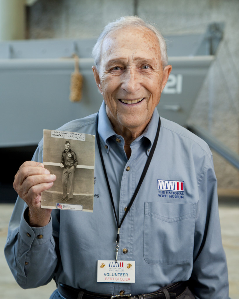 Bet Stolier holding a photo of himself during his World War II service.