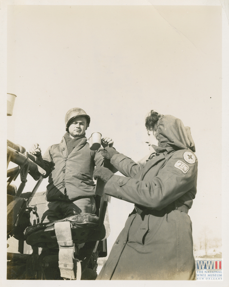 Lee Harris of the American Red Cross offers coffee to Private Joe Bergles in Loiano, Italy on 2 January 1945.