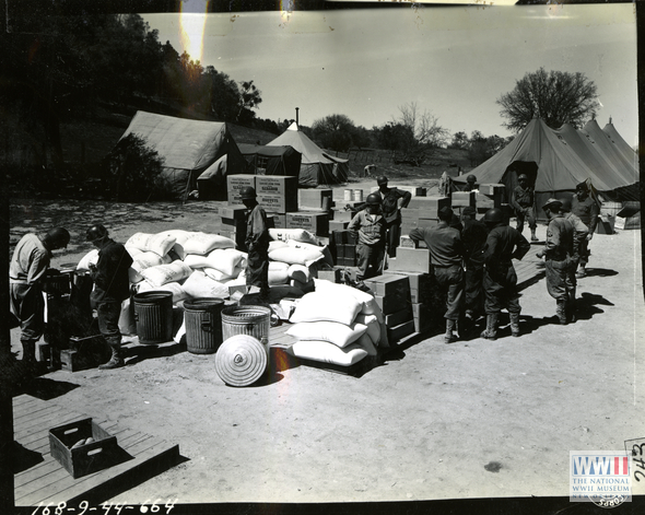 Flour, sugar, coffee, rice, cookies, and canned goods are distributed after ration breakdown at Hunter Liggett Military Base on  24 March 1944.