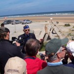 Dr. Harold Baumgarten speaks to a Museum tour group at Normandy, France, in 2006.