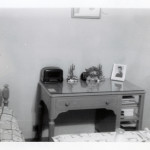 This bedside table holds a small radio next to a picture of a soldier.  From the collections of the NWWII Museum.