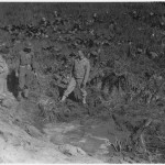 This is a photo of personnel from Fort Stevens examining craters from the shells fired on it.