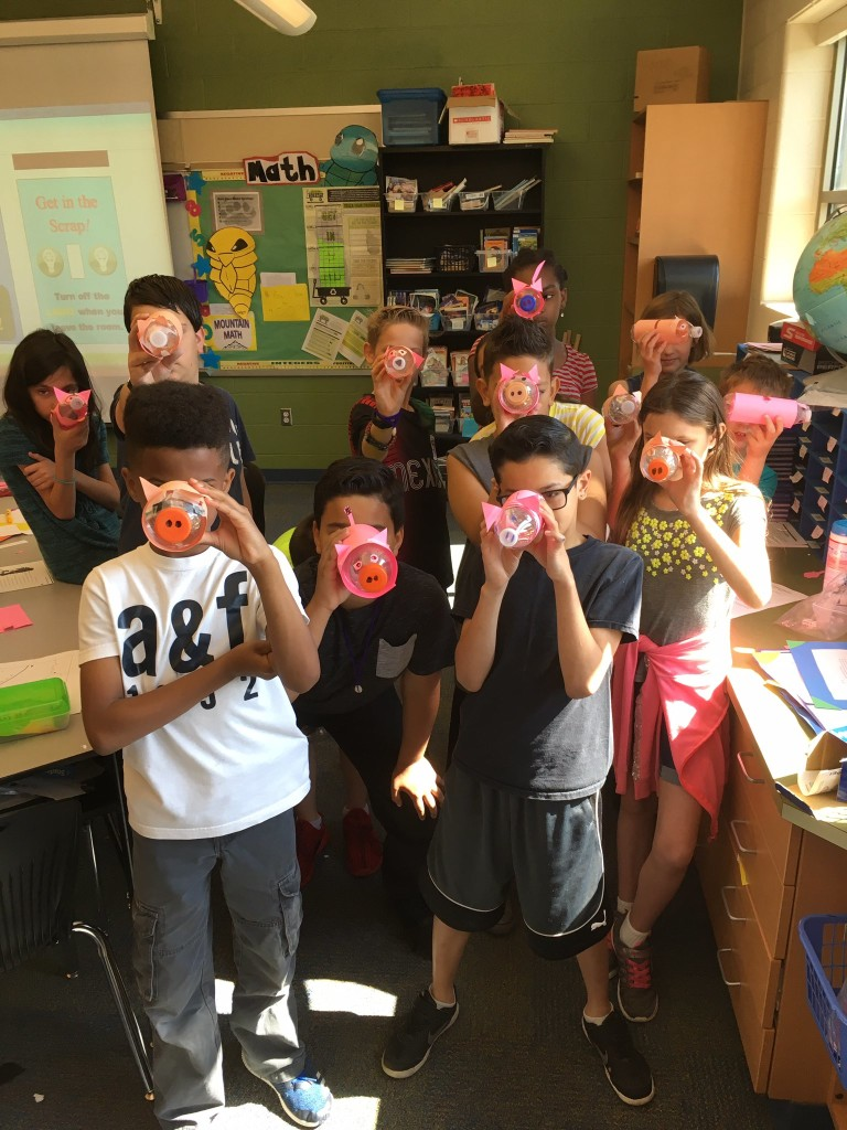 The Scraptastics from Bucher Elementary show off their wattle bottle piggy banks. Oink!